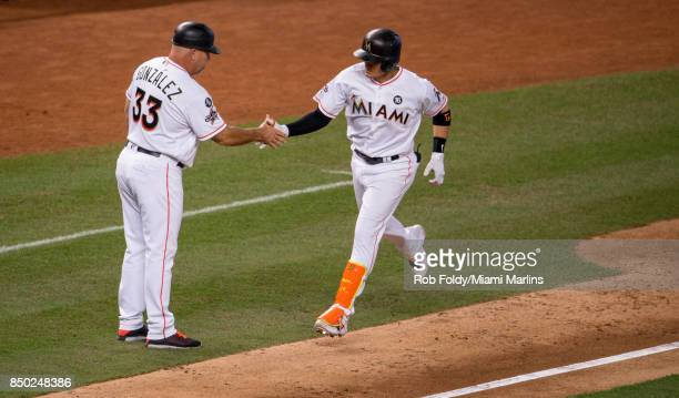Miguel Rojas of the Miami Marlins shakes hands with third base coach Fredi Gonzalez after hitting a home run during the eighth inning against the New...