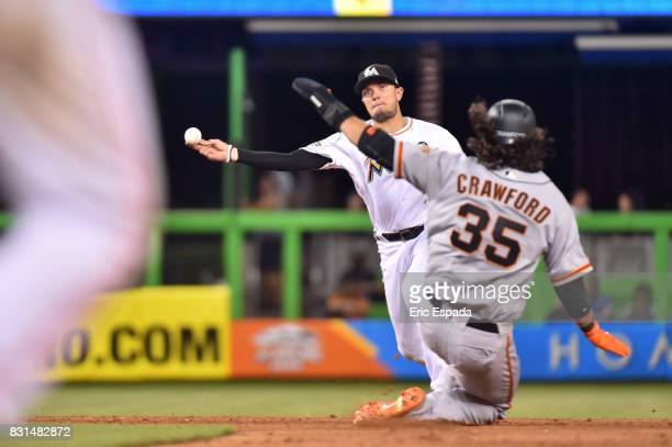 Miguel Rojas of the Miami Marlins shows towards first base as Brandon Crawford of the San Francisco Giants slides during the eighth inning at Marlins...