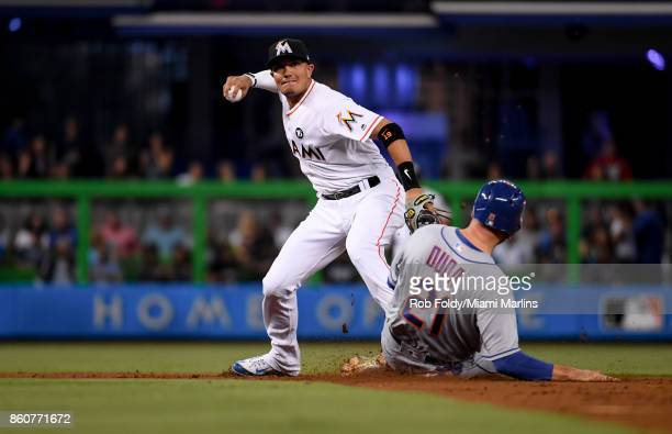 Miguel Rojas of the Miami Marlins throws over Lucas Duda of the New York Mets during the game at Marlins Park on April 14 2017 in Miami Florida