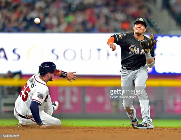 Miguel Rojas of the Miami Marlins turns a second inning double play against Tyler Flowers of the Atlanta Braves at SunTrust Park on September 8 2017...