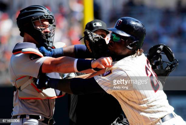 Miguel Sano of the Minnesota Twins and James McCann of the Detroit Tigers clash with home plate umpire Jordan Baker attempting to break up the...