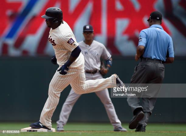 Miguel Sano of the Minnesota Twins rounds the bases after hitting a threerun home run as Starlin Castro of the New York Yankees and umpire Brian...
