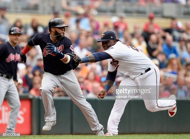 Miguel Sano of the Minnesota Twins tags out Carlos Santana of the Cleveland Indians after a rundown during the eighth inning in game one of a...