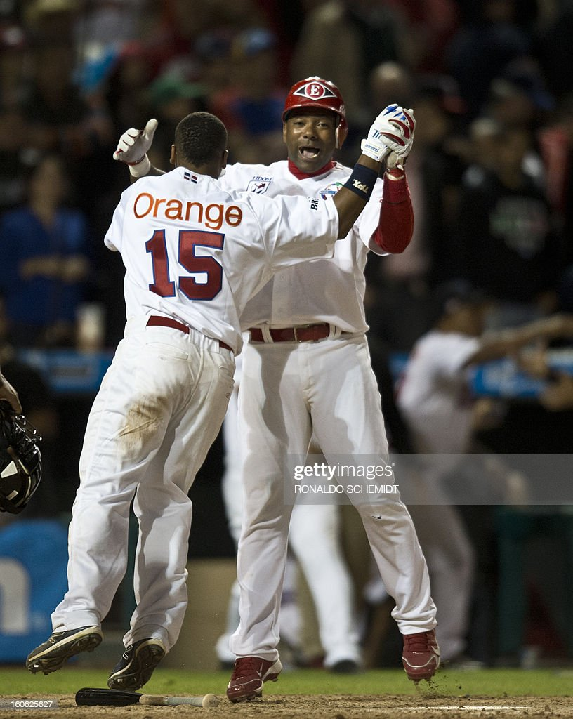Miguel Tejada (R) and Jose Ramirez of Leones del Escogido of Dominican Republic, celebrates his victory against Yaquis de Obregon of Mexico, during the 2013 Caribbean baseball series, on February 3, 2013, in Hermosillo, Sonora State, in the northern of Mexico. AFP PHOTO/Ronaldo Schemidt