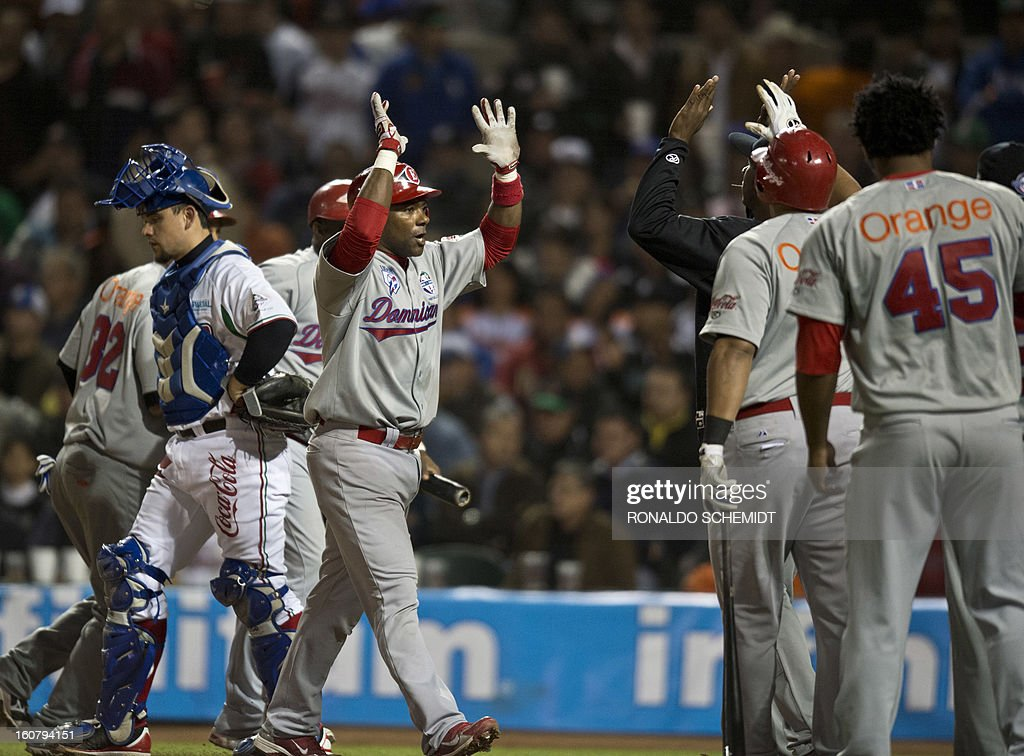 Miguel Tejada (C) of Leones del Escogido of Dominican Republic celebrates his home run against Yaquis de Obregon of Mexico during the 2013 Caribbean baseball series in Hermosillo, Sonora State, northern Mexico on February 5, 2013. AFP PHOTO / Ronaldo Schemidt