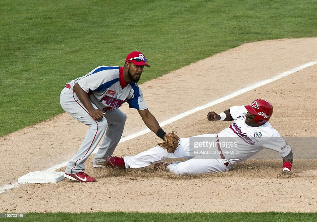 Miguel Tejada (R) of Leones del Escogido of Dominican Republic is put out in third base by Andy Gonzalez of Criollos de Caguas of Puerto Rico during the 2013 Caribbean baseball series, on February 4, 2013, in Hermosillo, Sonora State, in the northern of Mexico. AFP PHOTO/Ronaldo Schemidt