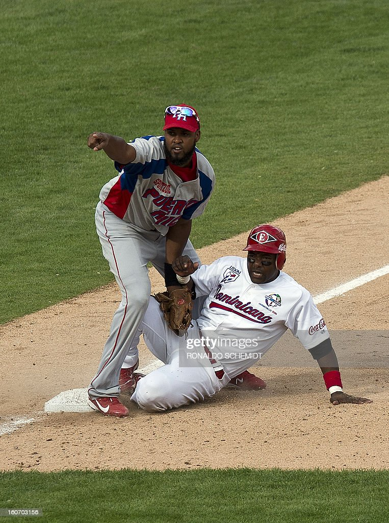 Miguel Tejada (R) of Leones del Escogido of Dominican Republic is tagged out in third base by Andy Gonzalez of Criollos de Caguas of Puerto Rico during the 2013 Caribbean baseball series, on February 4, 2013, in Hermosillo, Sonora State, in the northern of Mexico. AFP PHOTO/Ronaldo Schemidt