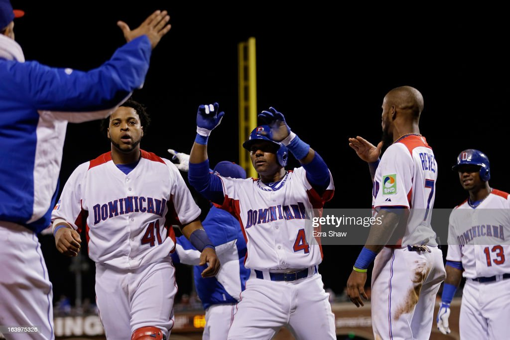 Miguel Tejada #4 of the Dominican Republic celebrates Carlos Santana #41 and Jose Reyes #7 after scoring in the fifth inning against the Netherlands during the semifinal of the World Baseball Classic at AT&T Park on March 18, 2013 in San Francisco, California.