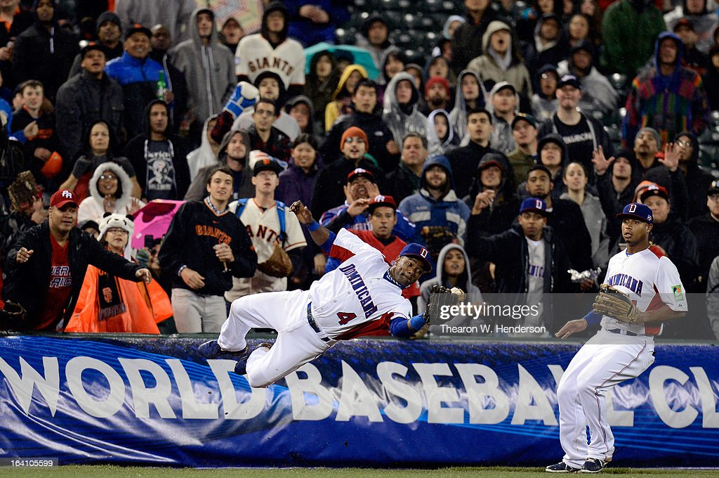 Miguel Tejada #4 of the Dominican Republic dives to make a catch in foul territory in the seventh inning as Moises Sierra #14 look on against Puerto Rico during the Championship Round of the 2013 World Baseball Classic at AT&T Park on March 19, 2013 in San Francisco, California.