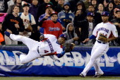 Miguel Tejada of the Dominican Republic dives to make a catch in foul territory in the seventh inning as Moises Sierra look on against Puerto Rico...