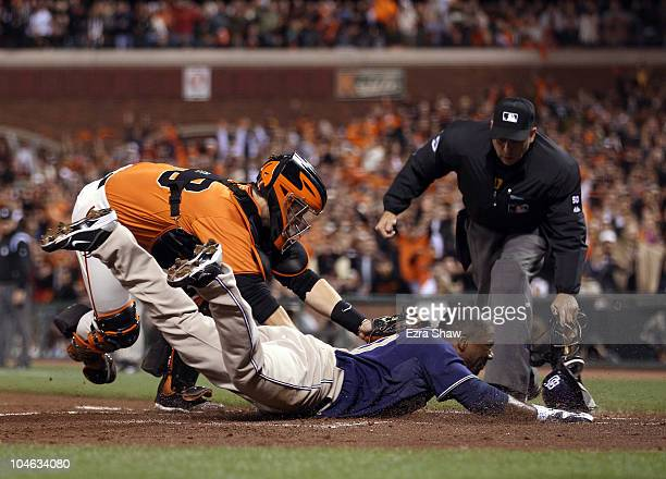 Miguel Tejada of the San Diego Padres is tagged out by Buster Posey of the San Francisco Giants when Tejada tried to score from first base on a hit...
