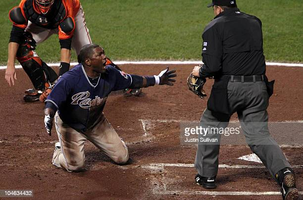 Miguel Tejada of the San Diego Padres reacts after being tagged out at home plate by Buster Posey of the San Francisco Giants during the first inning...
