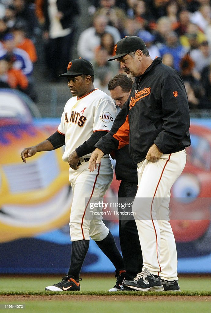 Miguel Tejada #10 of the San Francisco Giants gets hurt attempting to field a ground ball and is escorted off the field by trainer Dave Groeschner and manager Bruce Bochy #15 against the Los Angeles Dodgers in the third inning during an MLB baseball game at AT&T Park July 18, 2011 in San Francisco, California.