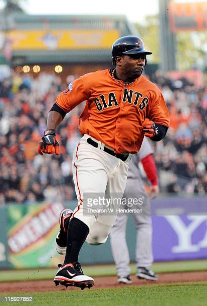 Miguel Tejada of the San Francisco Giants rounds third base and scores against the Cincinnati Reds in the first inning during a MLB baseball game...