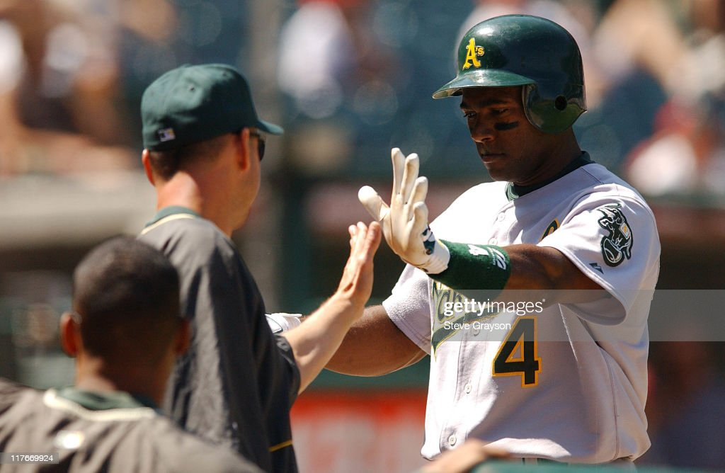 Miguel Tejeda of the A's is greeted in the dugout after scoing on a <a gi-track='captionPersonalityLinkClicked' href=/galleries/search?phrase=Scott+Hatteberg&family=editorial&specificpeople=239531 ng-click='$event.stopPropagation()'>Scott Hatteberg</a> double in the second inning.