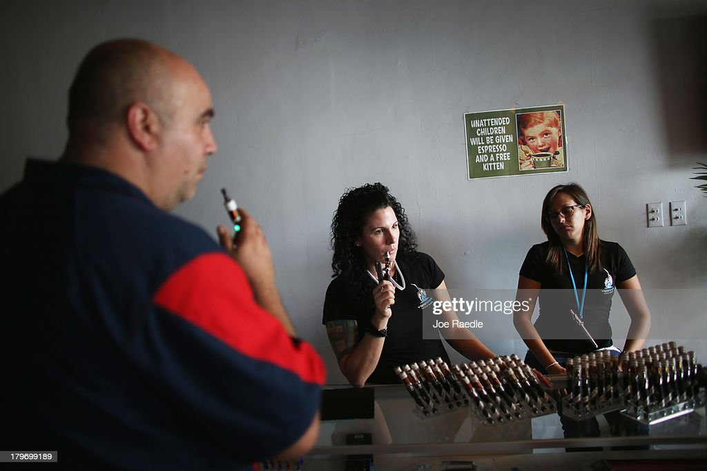 Miguel Tirado (L) shops for an E liquid for his electronic cigarette as Julia Boyle (C) and Michele Mendez, sales associate, help him at the Vapor Shark store on September 6, 2013 in Miami, Florida. E-cigarette manufacturers have seen a surge in popularity for the battery-powered devices that give users a vapor filled experience with nicotine and other additives, like flavoring.