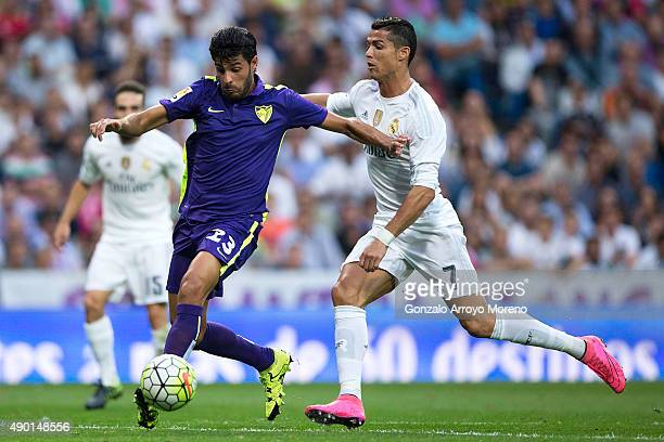 Miguel Torres of Malaga CF competes for the ball with Cristiano Ronaldo of Real Madrid CF during the La Liga match between Real Madrid CF and Malaga...