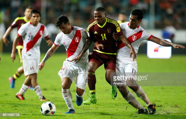 Miguel Trauco and Jhon Murillo of Venezuela fight for the ball with Renato Tapia of Peru during a match between Venezuela and Peru as part of FIFA...
