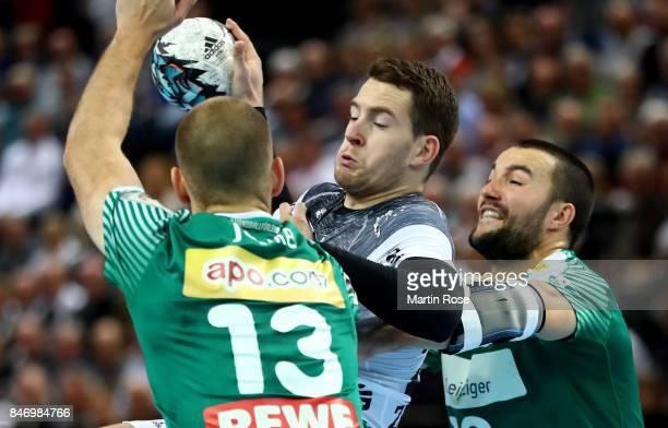 Miha Zarabec of Kiel challenges Bastian Roscheck and Maximilian Janke of Leipzig for the ball during the DKB HBL Bundesliga match between THW Kiel...