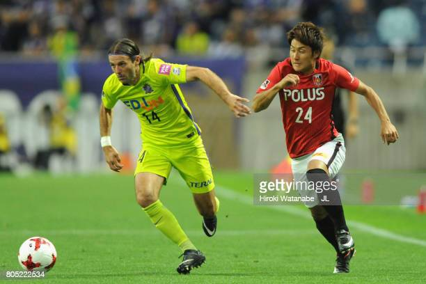 Mihael Mikic of Sanfrecce Hiroshima and Takahiro Sekine of Urawa Red Diamonds compete for the ball during the JLeague J1 match between Urawa Red...