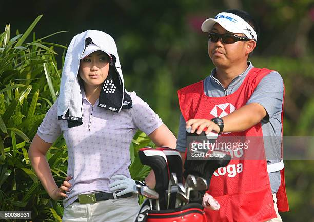 Miho Koga of Japan waits with her caddie on the second hole during the first round of the HSBC Women's Champions at Tanah Merah Country Club on...