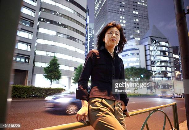 Miho Marui a former contract employee at KDDI Evolva Inc poses for a photograph in front of the KDDI building center in the Shinjuku district of...