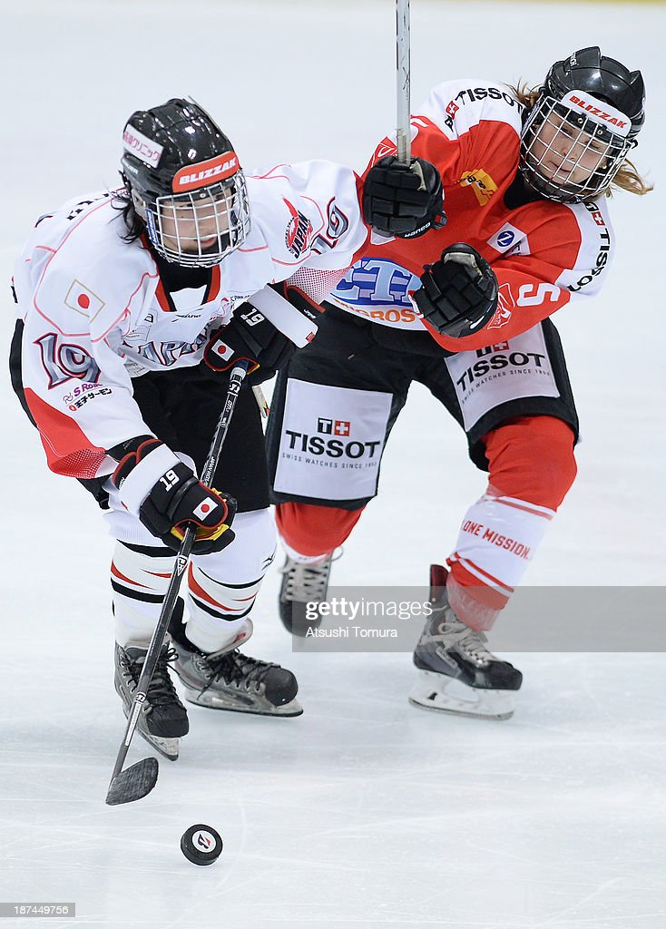 Miho Shishiuchi (L) of Japan and Livia Altmann (R) of Switzerland battles for the ball in the match between Japan and Switzerland during day three of the Ice Hockey Women's 5 Nations Tournament at the Shin Yokohama Skate Center on November 9, 2013 in Yokohama, Japan.