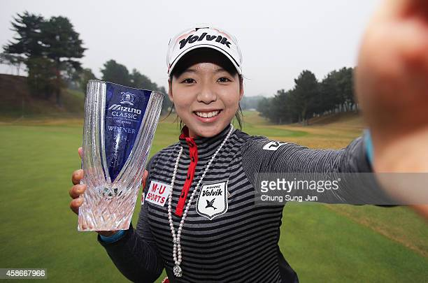 MiHyang Lee of South Korea imitates a 'selfie' as she poses with the trophy during a ceremony following the Mizuno Classic at Kintetsu Kashikojima...