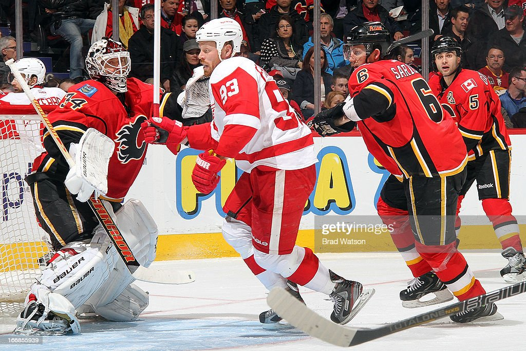 <a gi-track='captionPersonalityLinkClicked' href=/galleries/search?phrase=Miikka+Kiprusoff&family=editorial&specificpeople=171703 ng-click='$event.stopPropagation()'>Miikka Kiprusoff</a> #34 and <a gi-track='captionPersonalityLinkClicked' href=/galleries/search?phrase=Cory+Sarich&family=editorial&specificpeople=204153 ng-click='$event.stopPropagation()'>Cory Sarich</a> #6 of the Calgary Flames defend against <a gi-track='captionPersonalityLinkClicked' href=/galleries/search?phrase=Johan+Franzen&family=editorial&specificpeople=624356 ng-click='$event.stopPropagation()'>Johan Franzen</a> #93 of the Detroit Red Wings on April 17, 2013 at the Scotiabank Saddledome in Calgary, Alberta, Canada.