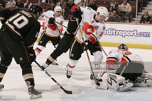 Miikka Kiprusoff and Michael Cammalleri of the Calgary Flames defend in the crease against Corey Perry of the Anaheim Ducks during the game on...