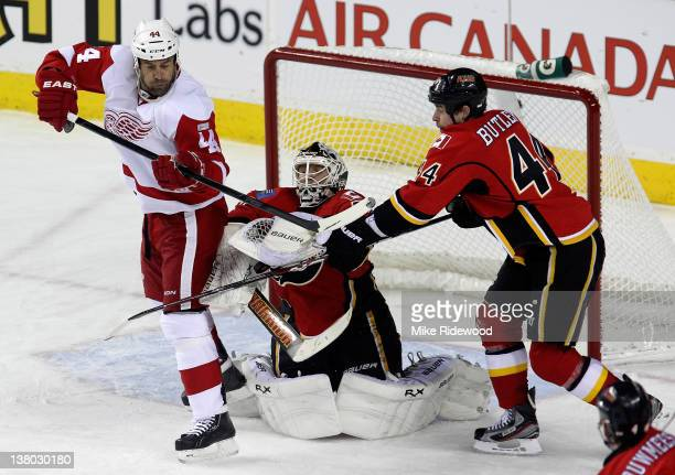 Miikka Kiprusoff grabs the puck with help from Chris Butler of the Calgary Flames against Todd Bertuzzi of the Detroit Red Wings in first period NHL...