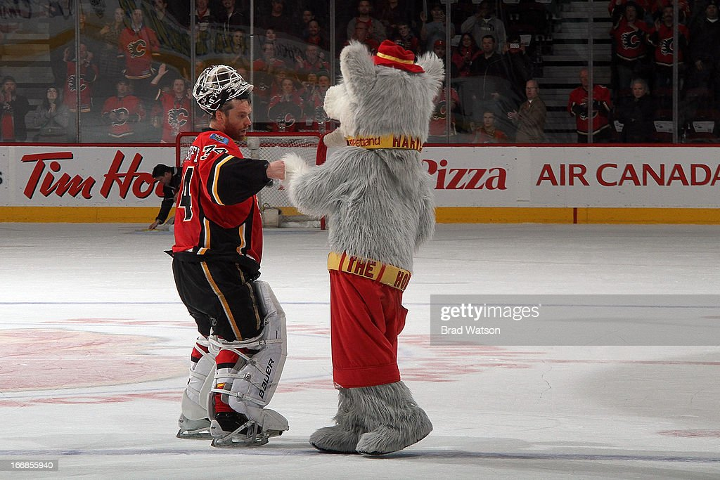 Miikka Kiprusoff of the Calgary Flames is congratulated by mascot Harvey the Hound after being named first star of the game against the Detroit Red...