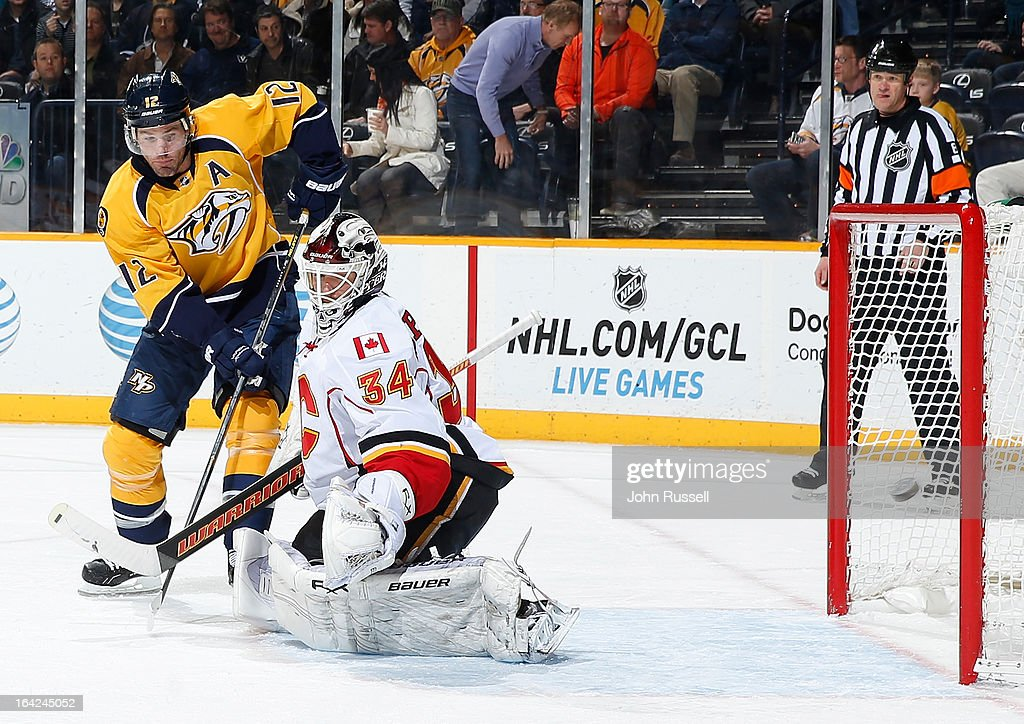 Miikka Kiprusoff #34 of the Calgary Flames lets a shot from Martin Erat #10 (not in frame) of the Nashville Predators in the net as Mike Fisher #12 battles during an NHL game at the Bridgestone Arena on March 21, 2013 in Nashville, Tennessee.
