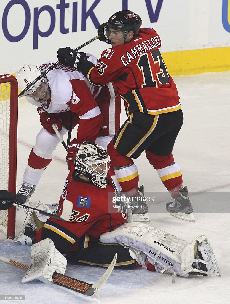 <a gi-track='captionPersonalityLinkClicked' href=/galleries/search?phrase=Miikka+Kiprusoff&family=editorial&specificpeople=171703 ng-click='$event.stopPropagation()'>Miikka Kiprusoff</a> #34 of the Calgary Flames makes a save as teammate <a gi-track='captionPersonalityLinkClicked' href=/galleries/search?phrase=Mike+Cammalleri&family=editorial&specificpeople=634009 ng-click='$event.stopPropagation()'>Mike Cammalleri</a> #13 keeps <a gi-track='captionPersonalityLinkClicked' href=/galleries/search?phrase=Justin+Abdelkader&family=editorial&specificpeople=2271858 ng-click='$event.stopPropagation()'>Justin Abdelkader</a> #8 of the Detroit Red Wings away during third period NHL action on March 13, 2013 at the Scotiabank Saddledome in Calgary, Alberta, Canada. Calgary Flames defeated the Detroit Red Wings 5 - 2.