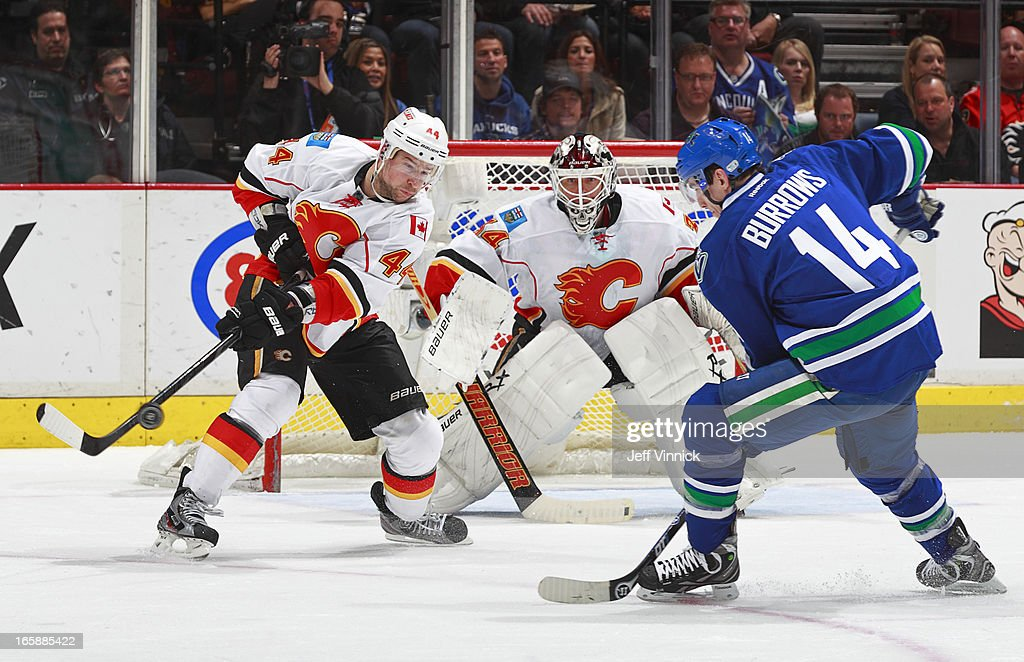 <a gi-track='captionPersonalityLinkClicked' href=/galleries/search?phrase=Miikka+Kiprusoff&family=editorial&specificpeople=171703 ng-click='$event.stopPropagation()'>Miikka Kiprusoff</a> #34 of the Calgary Flames watches Chris Butler #44 of the Flames and <a gi-track='captionPersonalityLinkClicked' href=/galleries/search?phrase=Alexandre+Burrows&family=editorial&specificpeople=592489 ng-click='$event.stopPropagation()'>Alexandre Burrows</a> #14 of the Vancouver Canucks slap at the puck during their NHL game at Rogers Arena April 6, 2013 in Vancouver, British Columbia, Canada. Vancouver won 5-2