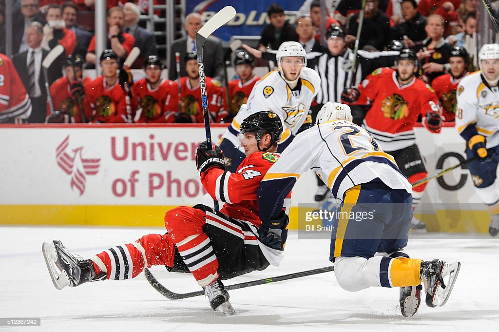 Miikka Salomaki #20 of the Nashville Predators pushes into Richard Panik #14 of the Chicago Blackhawks during the NHL game at the United Center on February 25, 2016 in Chicago, Illinois.