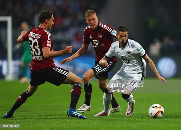Mijat Gacinovic of Eintracht Frankfurt evades Georg Margreitter and Hanno Behrens of Nuernburg during the Bundesliga Playoff final second leg match...
