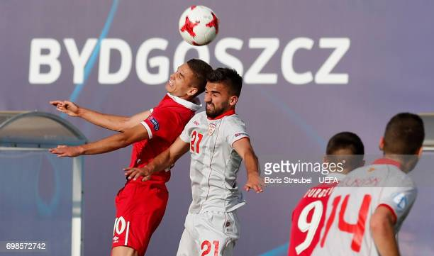 Mijat Gacinovic of Serbia jumps for a header with Mevlan Murati of FYR Macedonia during the UEFA European Under21 Championship match between Serbia...