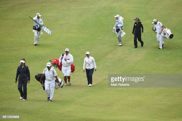 MiJeong Jeon of South Korea Eri Okayama of Japan and Asako Fujimoto of Japan walk off the course as play is suspended due to bad weather during the...