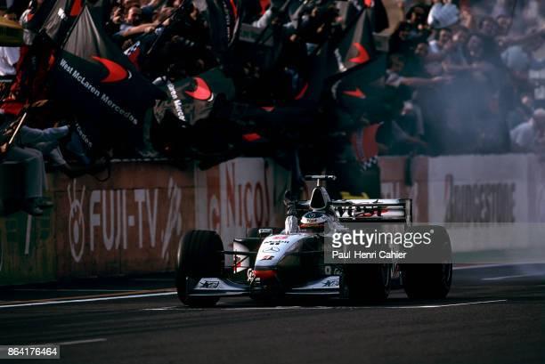 Mika Häkkinen McLarenMercedes MP413 Grand Prix of Japan Suzuka Circuit 01 November 1998 Mika Häkkinen waves as he crosses the finish line to...
