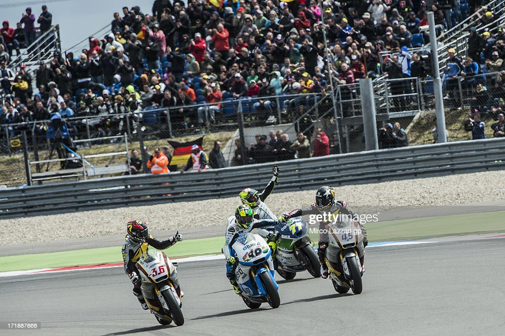 (L-R Mika Kallio of Finland and Marc VDS Racing Team, Pol Espargaro of Spain and Pons 40 HP Tuenti, Dominique Aegerter of Switzerland and Technomag CarXpert and Scott Redding of Great Britain and Marc VDS Racing Team congratulate and greet the fans during the Moto2 race during the MotoGp Of Holland - Race at TT Circuit Assen on June 29, 2013 in Assen, Netherlands.