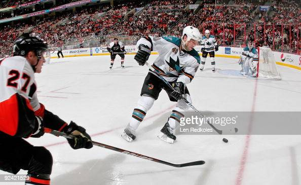 Mika Pyorala of the Philadelphia Flyers attempts to break up the back handed pass of Kent Huskins of the San Jose Sharks on October 25 2009 at the...