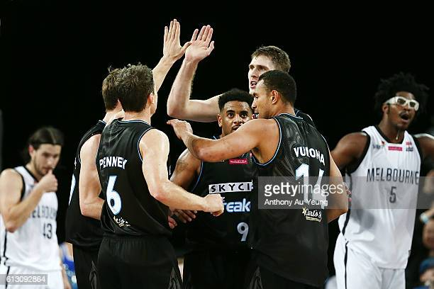 Mika Vukona Kirk Penney and Corey Webster of New Zealand celebrate during the round one NBL match between the New Zealand Breakers and Melbourne...
