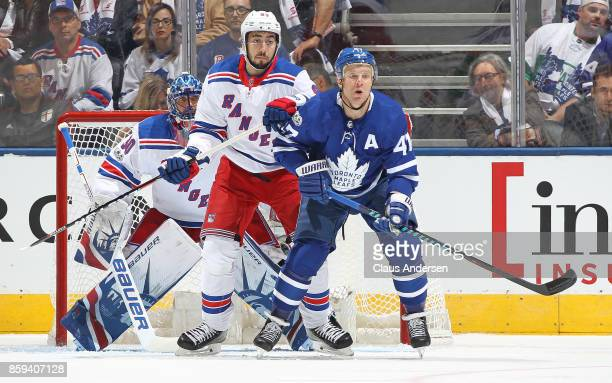 Mika Zibanejad of the New York Rangers battles against Leo Komarov of the Toronto Maple Leafs in an NHL game at the Air Canada Centre on October 7...