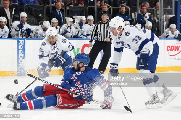 Mika Zibanejad of the New York Rangers battles for the puck against JT Brown and Greg McKegg of the Tampa Bay Lightning at Madison Square Garden on...