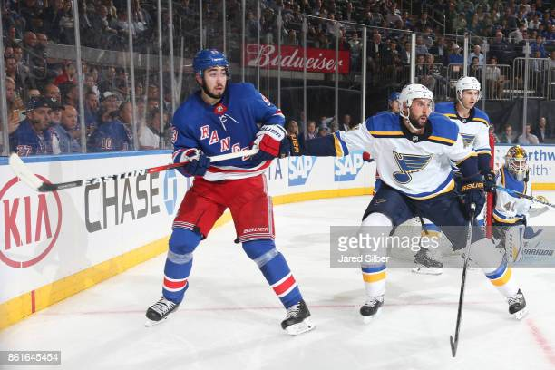 Mika Zibanejad of the New York Rangers skates against Robert Bortuzzo of the St Louis Blues at Madison Square Garden on October 10 2017 in New York...