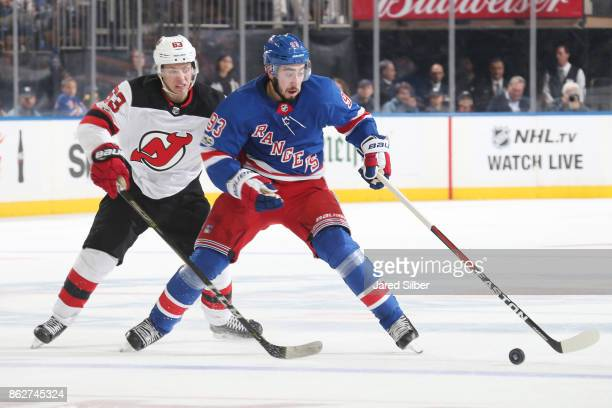 Mika Zibanejad of the New York Rangers skates with the puck against Jesper Bratt of the New Jersey Devils at Madison Square Garden on October 14 2017...