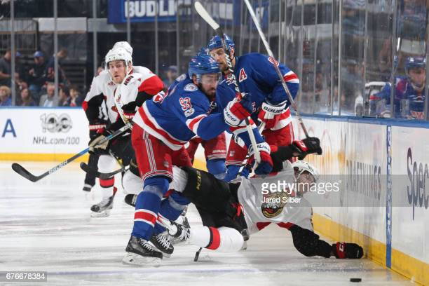 Mika Zibanejad of the New York Rangers throws a hit against Mike Hoffman of the Ottawa Senators in Game Three of the Eastern Conference Second Round...