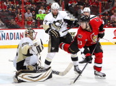 Mika Zibanejad of the Ottawa Senators battles for position against Paul Martin of the Pittsburgh Penguins as Tomas Vokoun guards his net in Game Four...