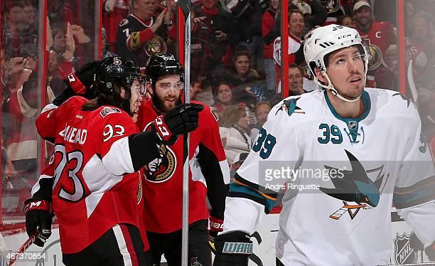 Mika Zibanejad of the Ottawa Senators celebrates his first period goal with teammate Eric Gryba as Logan Couture of the San Jose Sharks looks away at...